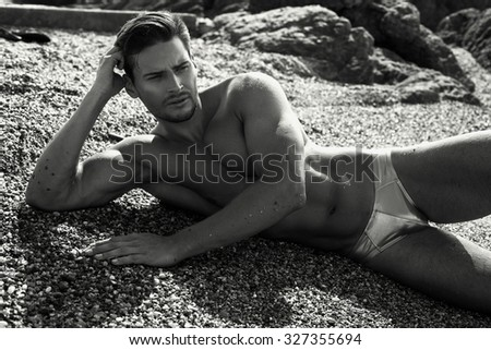 Black and white photo of young model lying on the beach - stock photo