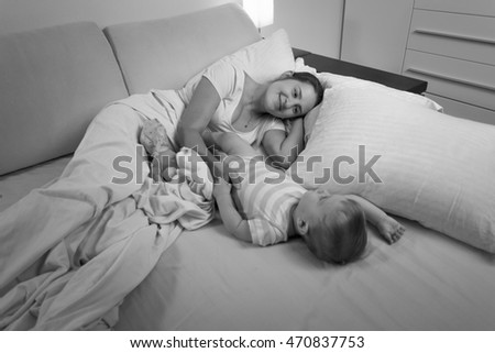 Black and white photo of young mother sleeping with her baby boy in bed