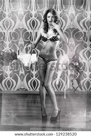 Black and white photo of young sexy woman drying the linen. Pin-up style. - stock photo