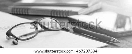 black-and-white photo.  Office desk with business objects - open notebook, tablet computer, glasses, pencil, pen. Free space for text. Office workplace
