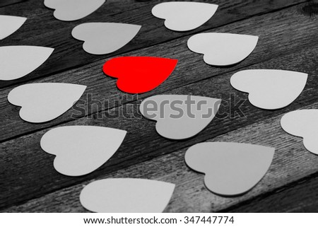 Black and white photo with paper stickers for messages in the shape of a heart, one red laid out in rows diagonally. The concept of love, romance, Valentine's day. Copy space - stock photo