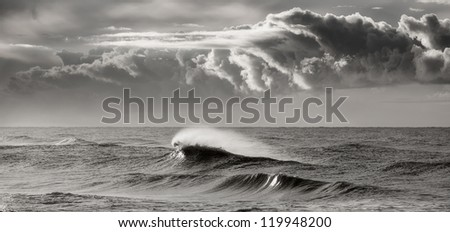 Black and white photograph of a wave breaking beneath a storm sky