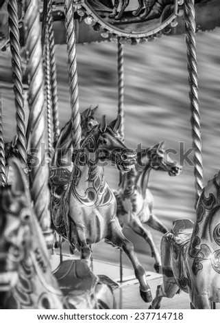 Black And White Photograph Of Vintage Steam Carousel Horses With Motion Blur - stock photo