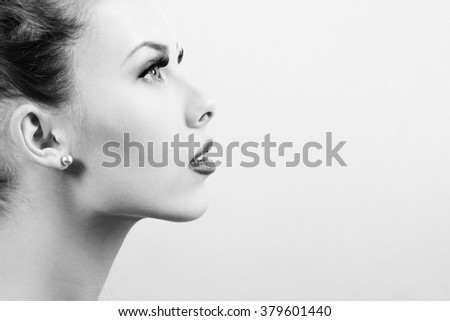 Black and white photography closeup of beautiful young woman on light background