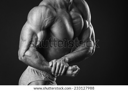 Black and white photography. Handsome muscular guy, bodybuilder, posing on a black background. Traced muscles, posing, sports, muscle power - the concept of sport of bodybuilding.