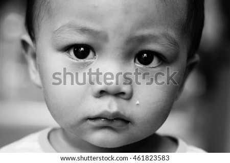 Black and white photography of an asian boy with sad face looking at camera