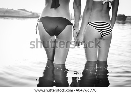 Black and white photography of 2 beautiful young women with perfect fitness shape buttocks having fun posing on summer water background outside - stock photo