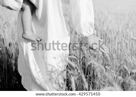Black and white photography of female in ethnic clothes holding kid and walking across wheat field on summer day - stock photo