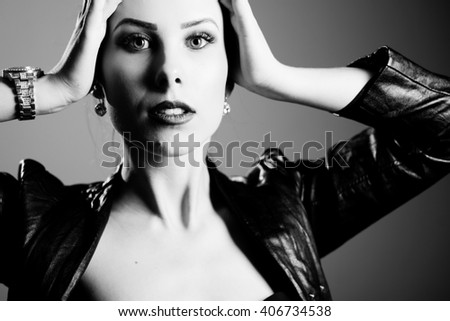 Black and white photography of hot sexy pretty young lady wearing leather jacket sensually looking at camera on grey background, picture closeup - stock photo