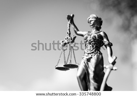 Black and white photography of sculpture of themis, femida or justice goddess on bright sky copy space background - stock photo