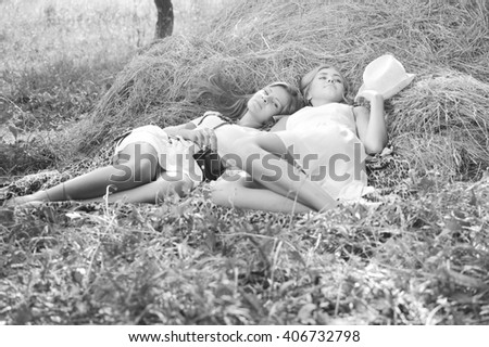 Black and white photography of two happy girl friends lying on fresh dry hay and talking secrets closeup portrait