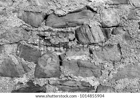 black and white picture of a wall made of stones.