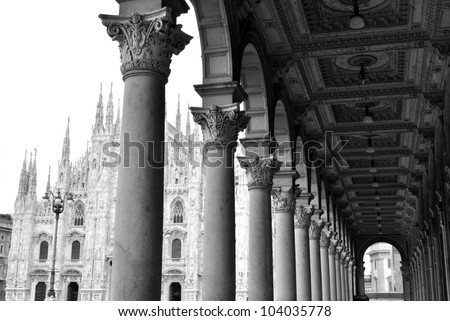 Black and white picture of ancient arcade and gothic cathedral of Milan, Lombardy, Italy - stock photo