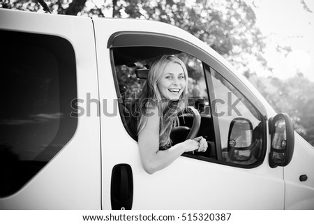 Black and white picture of beautiful young woman driving car. Girl looking from car window at camera on blurred countryside background.