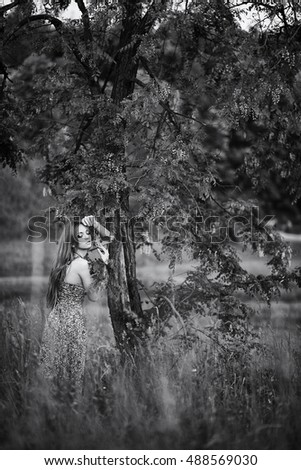 Black and white picture of gorgeous lady leaning to the tree
