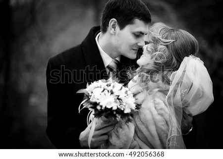 Black and white picture of groom leaning to bride for a kiss holding her shoulders tender