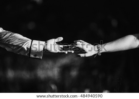 Black and white picture of hands touching with fingers over the grass