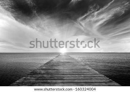 black and white picture of old bridge to the sea - stock photo