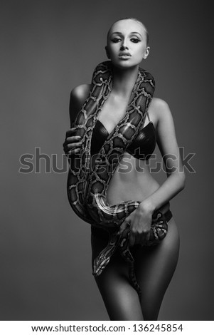 black and white picture of sexy young woman in bikini posing with python - stock photo