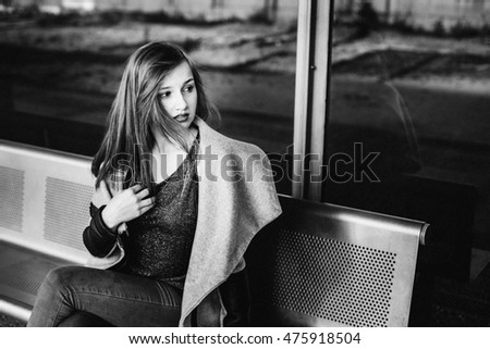 Black and white picture of stunning young woman sitting on steel bench