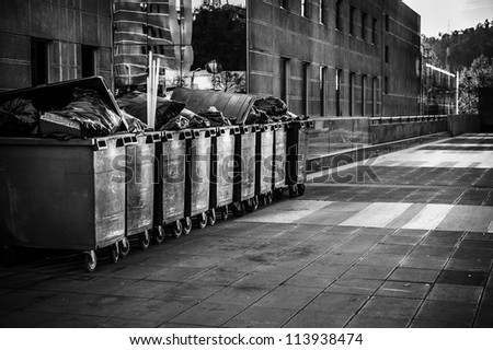 Black and white picture of trash cans in the street in the middle of corporate buildings - stock photo