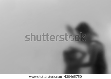 black and white picture Silhouette , women , violence against children. Behind frosted glass ( Blurring and noise concept ) pictures convey a depressed mood . Leave space for text - stock photo
