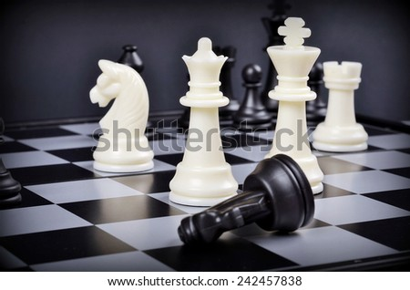 Black and white  pieces on a chess board  with shallow depth of field.