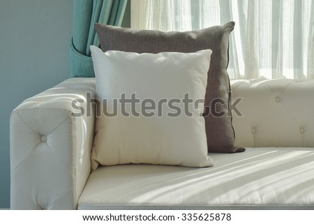 Black and white pillow on beige sofa with natural light in the living room - stock photo