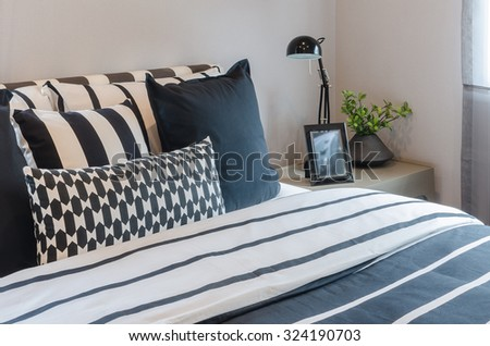 black and white pillows and blanket on bed with black lamp on table side in bedroom