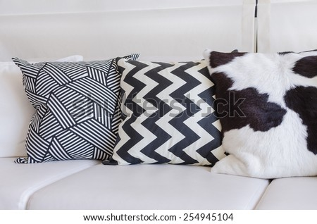 black and white pillows on white sofa in living room at home - stock photo