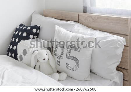 black and white pillows with doll on wooden bed in kid's bedroom at home - stock photo