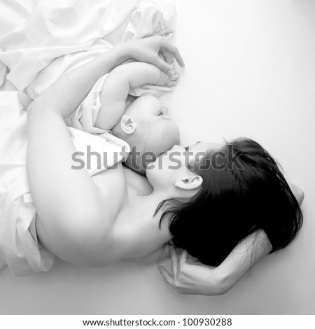 Black and white portrait - a young mother and her baby sleeping in bed. The symbol of maternal love, care, happiness and pacification - stock photo