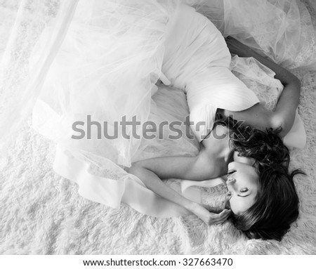 Black and white portrait, beautiful girl in a wedding dress with a gun, studio shooting