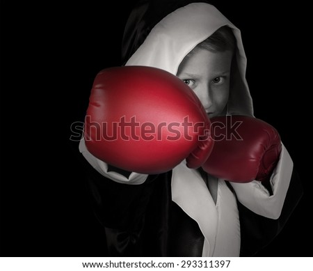 Black and white portrait little boy in red boxing gloves