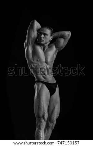 black and white portrait male athlete bodybuilder posing on a black background
