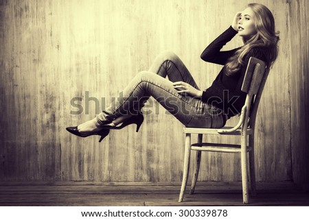 Black-and-white portrait of a beautiful blonde girl in jeans clothes posing by the grunge wall. Fashion. - stock photo