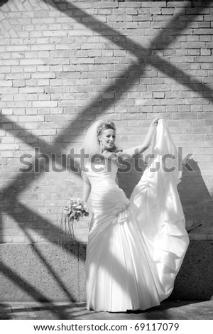 black and white portrait of a beautiful bride in a gown with a train