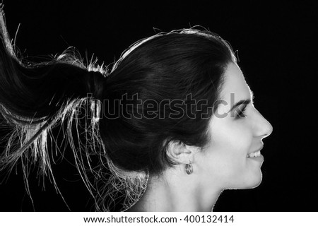 Black and white portrait of a beautiful smiling woman with ponytail