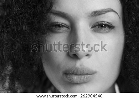 Black and white portrait of a beautiful woman frowning and looking upset. - stock photo