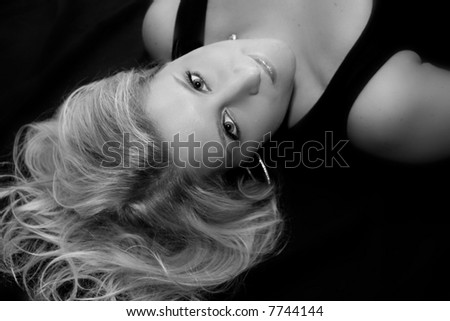 black and white portrait of a beautiful woman lying on black sheets