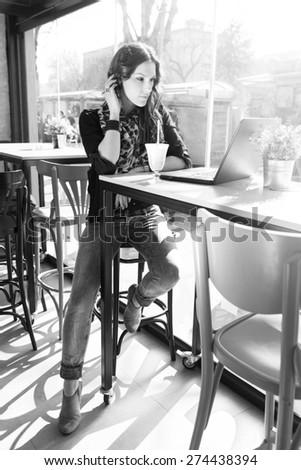 Black and white portrait of a beautiful woman using laptop in internet cafe - stock photo