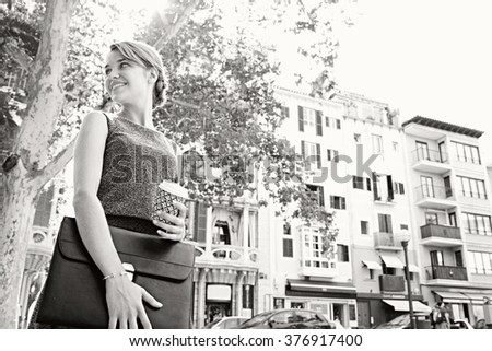 Black and white portrait of a beautiful young business woman commuter in classic buildings city, holding a coffee paper cup. Professional businesswoman drinking coffee, on the go lifestyle exterior. - stock photo