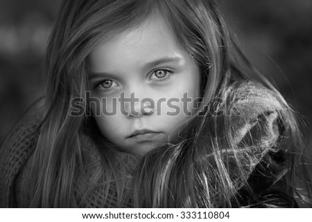 black and white portrait of a beautiful young girl with long hair taken outside - stock photo