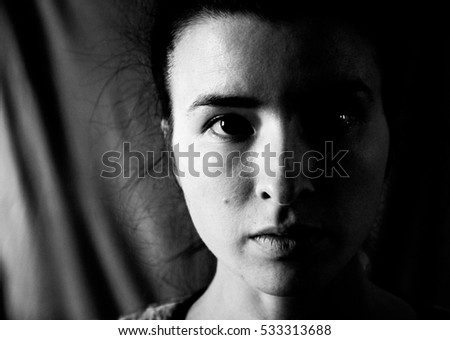 Black and white portrait of a beautiful young woman looking at the camera, her face half lit by the sunlight coming from the window