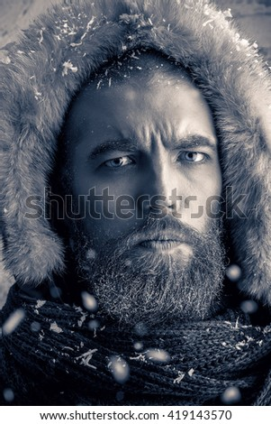 Black-and-white portrait of a brutal man with beard and mustache dressed in winter clothes, covered with frost. - stock photo