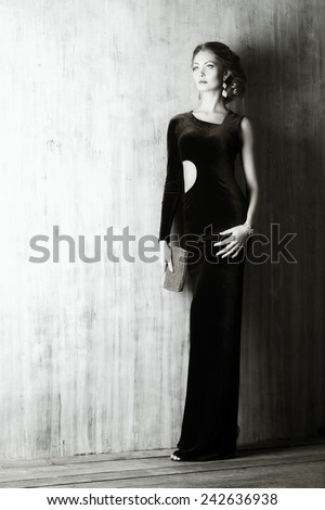 Black-and-white portrait of a charming young woman wearing elegant evening dress and beautiful hairstyle. Jewellery.  Fashion shot. Full length portrait.