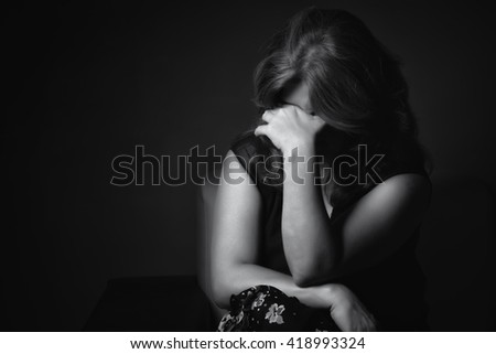 Black and white portrait of a crying sad and depressed woman with a dark background - stock photo