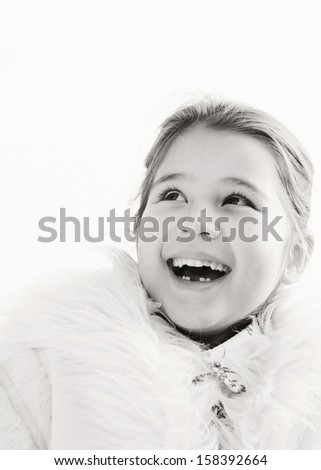 Black and white portrait of a cute young girl child laughing and being joyful while in a park during a sunny winter day, looking up to the sky and wearing a warm coat, outdoors. - stock photo