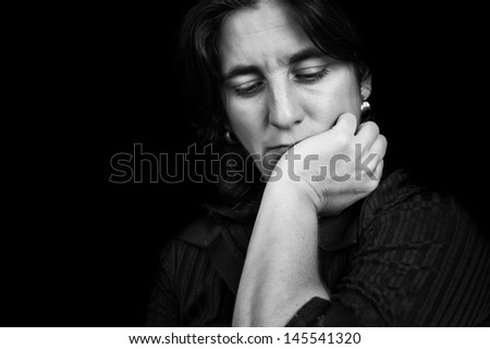 Black and white portrait of a depressed hispanic woman on a black background - stock photo