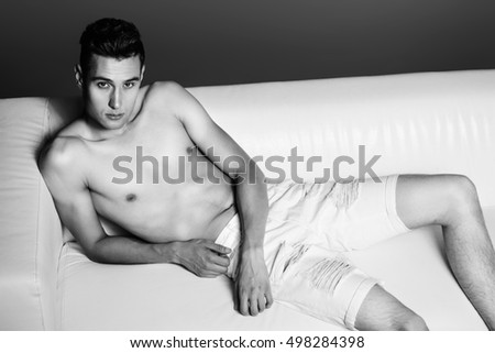 Black-and-white portrait of a handsome shirtless man lying on a couch. Men's beauty.